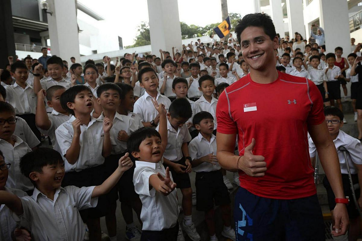 Joseph Schooling poses with ACS Junior students in the background.