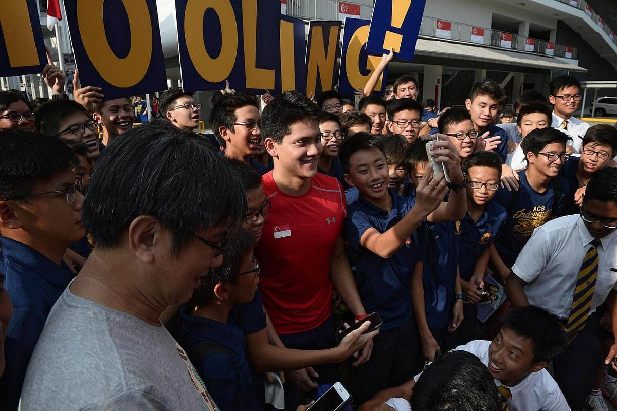 Joseph Schooling takes photographs with the ACS (I) swim team during his visit to ACS Junior.