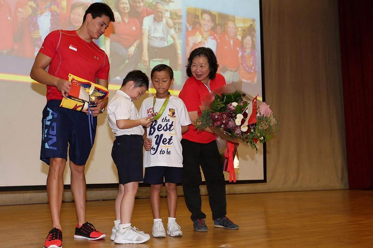 Darion Pang, 9, admiring Schooling's gold medal after receiving it from Schooling and then passing it on to Marcus Lim, 10, while May Schooling looks on.