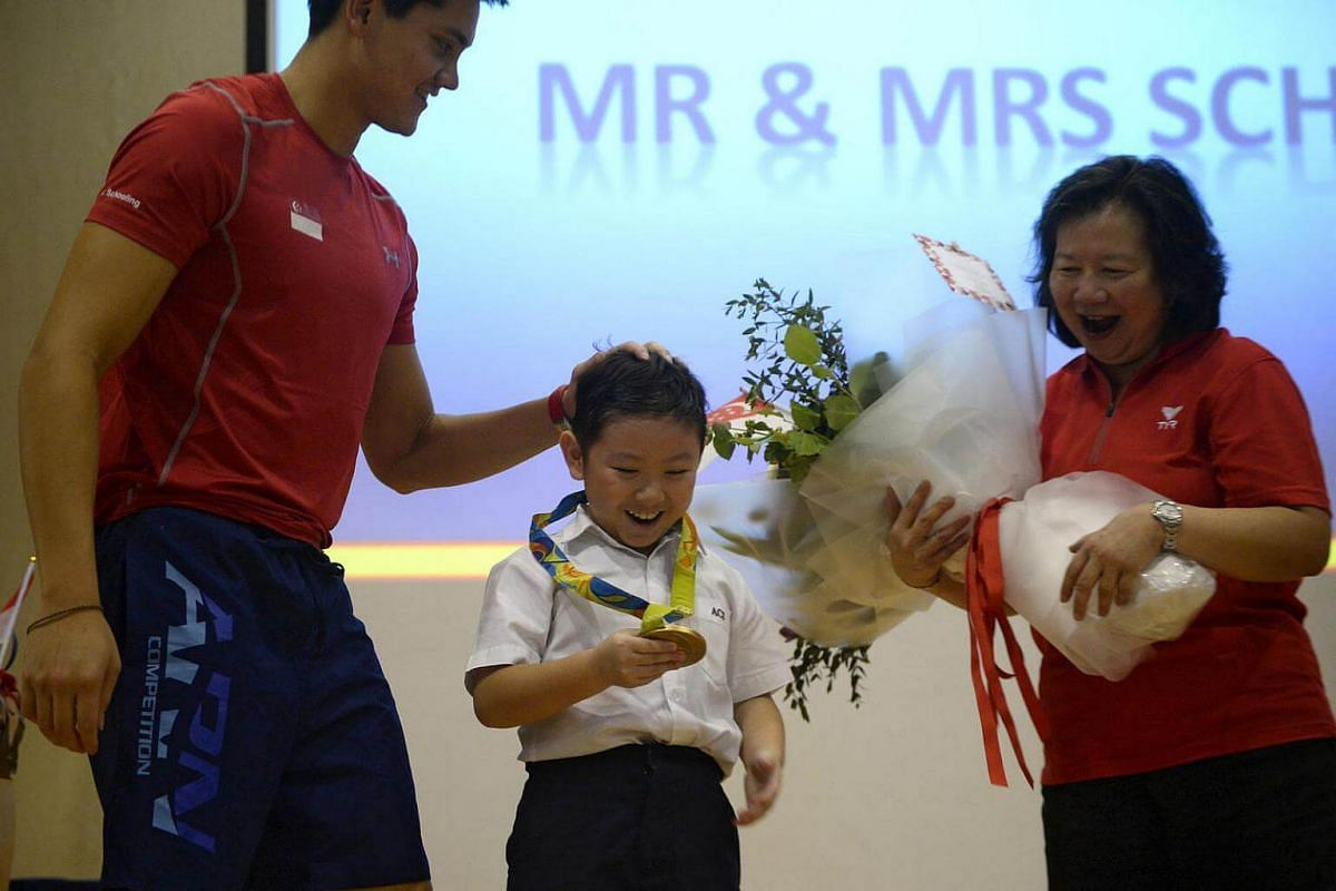 Joseph Schooling pats ACS Junior student Darion Pang, 9, as he poses with Schooling's gold medal, alongside his mother Mrs May Schooling at ACS Junior on August 15.