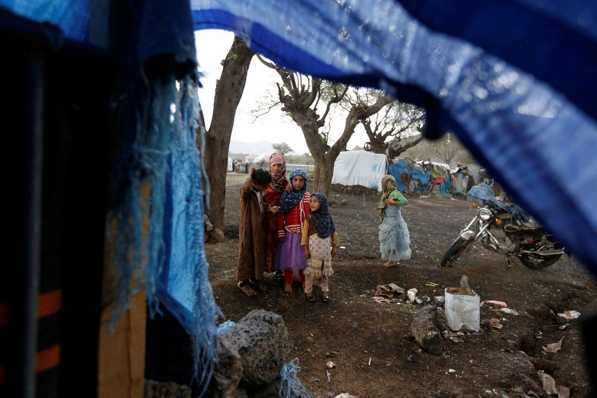 Children stand outside a tent at a camp for internally displaced people near Sanaa, Yemen on August 15.