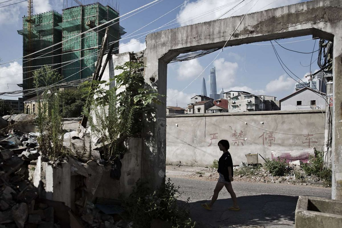 A pedestrian walks through a neighborhood slated for redevelopment as the Shanghai Tower stands in the distance in Shanghai, China, on August 15.