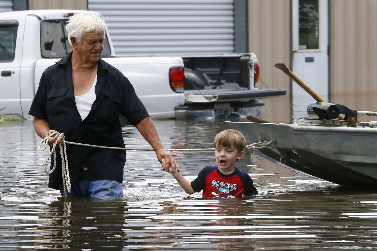 Richard Rossi and his four-year-old great grandson Justice wade through water in search of higher ground after their home took in water in St. Amant, Louisiana, US on August 15.