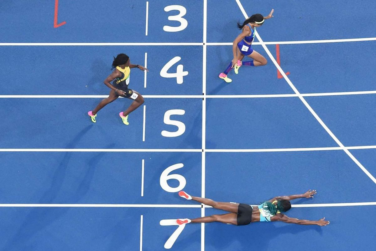 Bahamas' Shaunae Miller dives to cross the finish line ahead of US's Chase Kalisz during the Women's 400m Final during the athletics event at the Olympic Stadium in Rio de Janeiro on August 15.