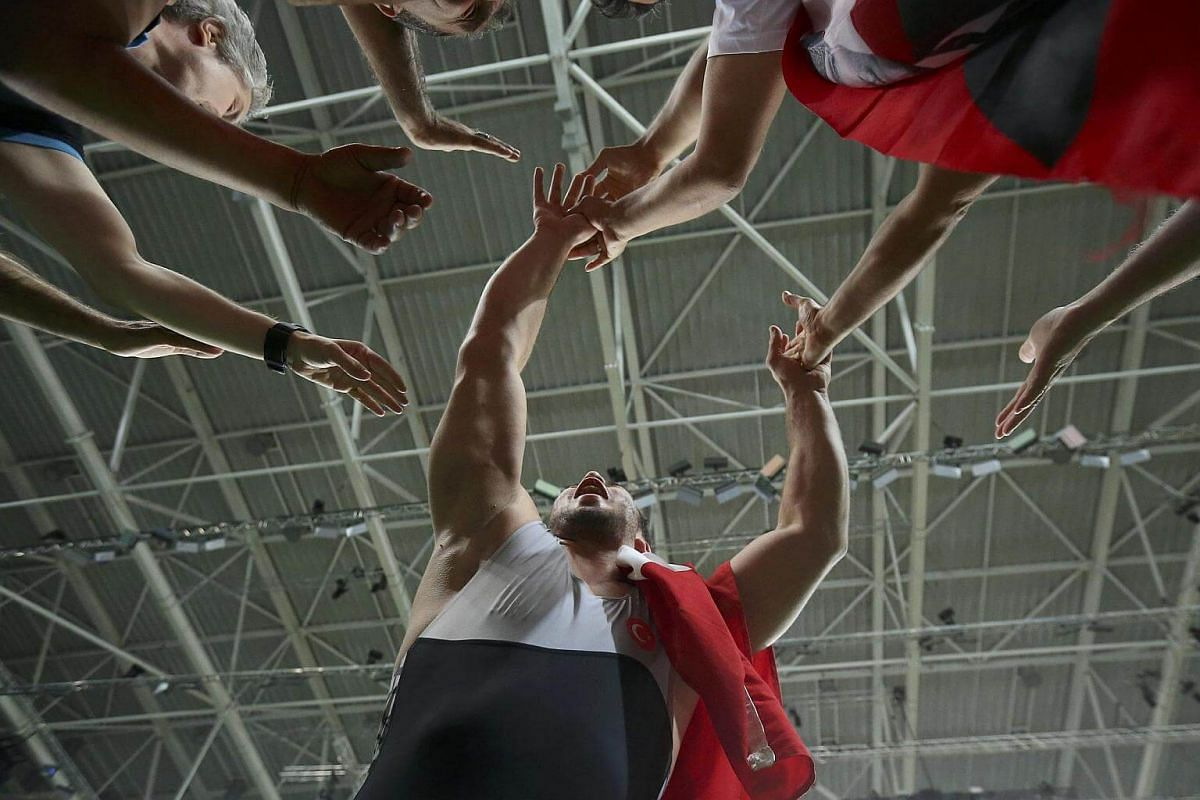 Cenk Ildem of Turkey celebrates with supporters winning the bronze medal.