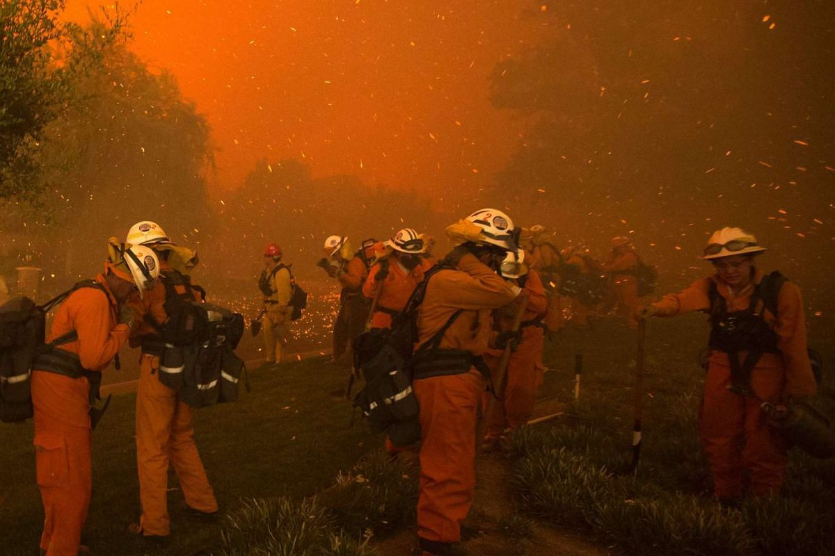 Inmate handcrew firefighters shield themselves from embers and heavy smoke as flames close in on houses at the Sand Fire near Santa Claritaon on July 23, 2016.