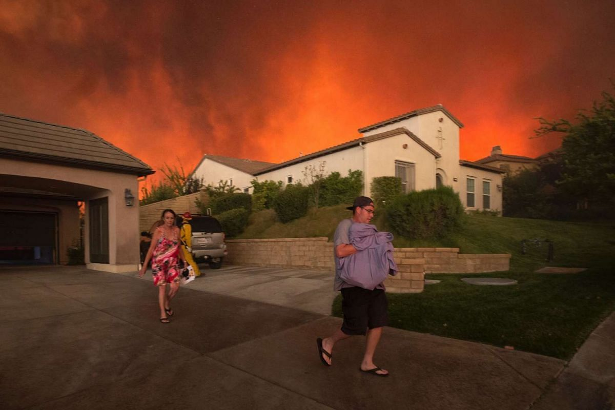 Residents flee their home as flames from the Sand Fire close in near Santa Clarita, California, on July 23, 2016.