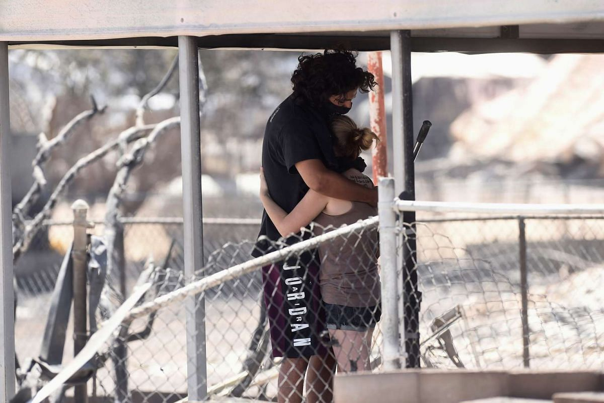 Brittany Thompson (right) hugs a companion after finding a dead dog at a residence that burned down after the Erskine Fire burned through South Lake, California, on June 24, 2016.