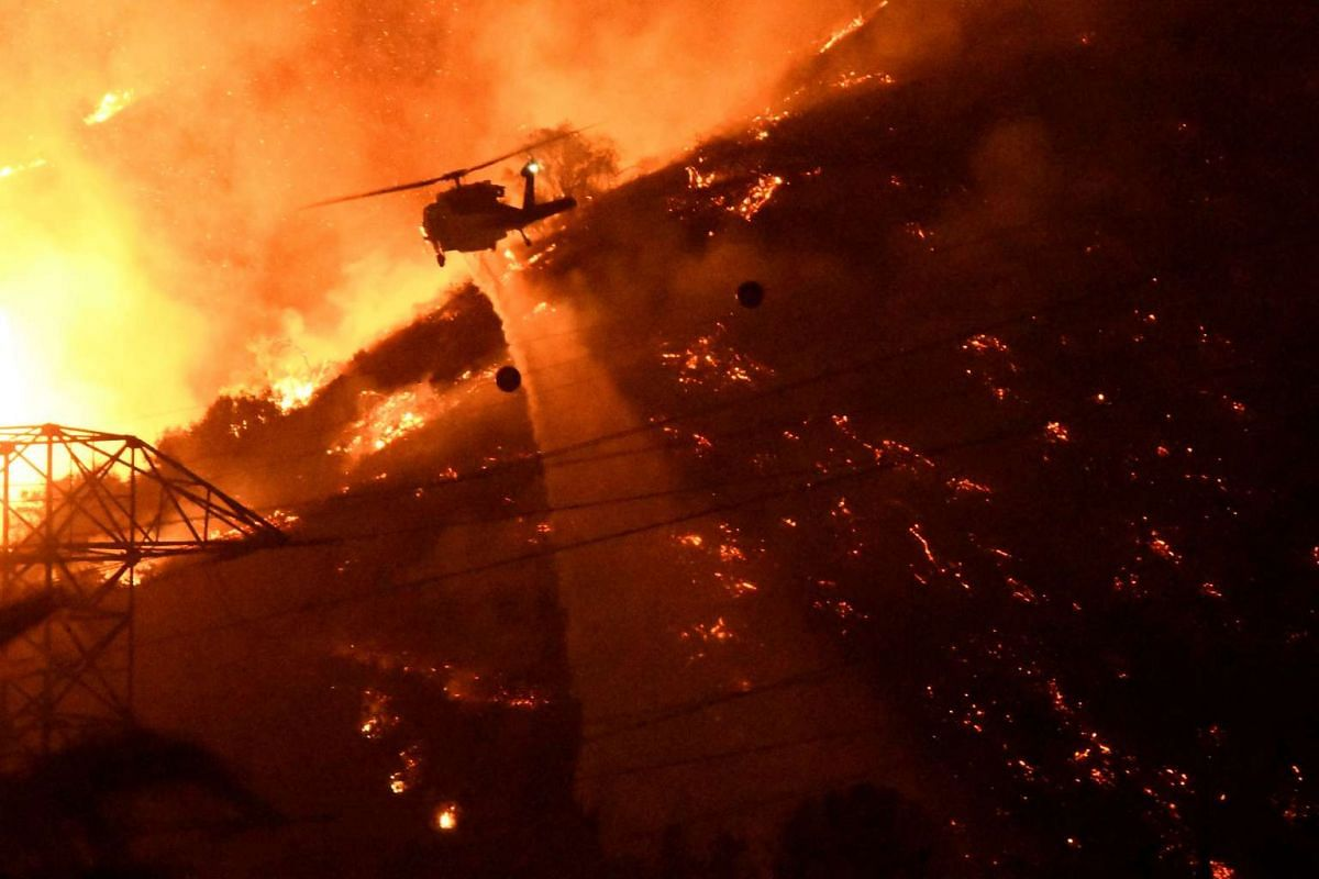 A Los Angeles County fire helicopter makes a night drop while battling the so-called Fish Fire above Azusa, California, on June 20, 2016.