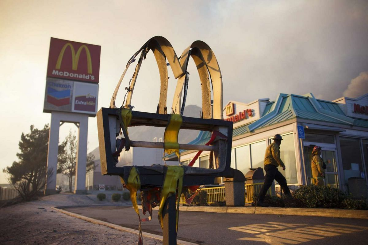 A melted sign from a McDonald's restaurant shows the damage as firefighters check the area after a wildfire swept through Cajon Junction, on Aug 16, 2016.