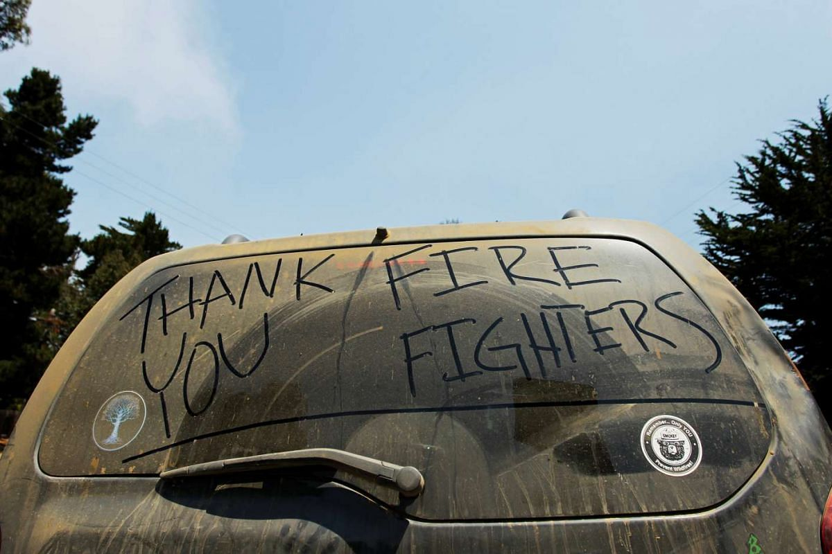 A note thanking firefighters is written on the dust covered rear window of a Big Sur resident's vehicle, during the Soberanes Fire, in Carmel Highlands, on July 30, 2016.
