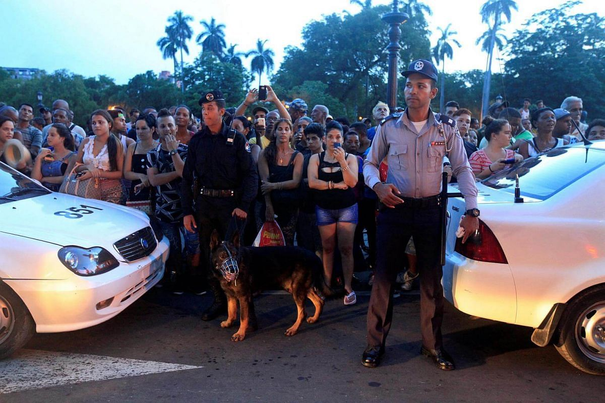 Cuban policemen stand guard near a hotel as people wait for the arrival of American pop star Madonna in Havana, Cuba, on Aug 15.