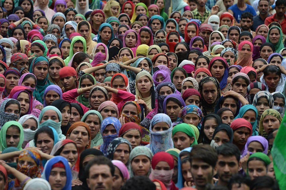 Kashmiri mourners look on during the funeral of four civilians at Aripanthan Magam village in Budgam district on the outskirts of Srinagar on August 16.