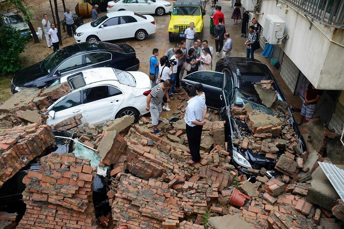 Cars are seen buried under a collapsed wall after a heavy rainfall in Yulin, China, on August 15.