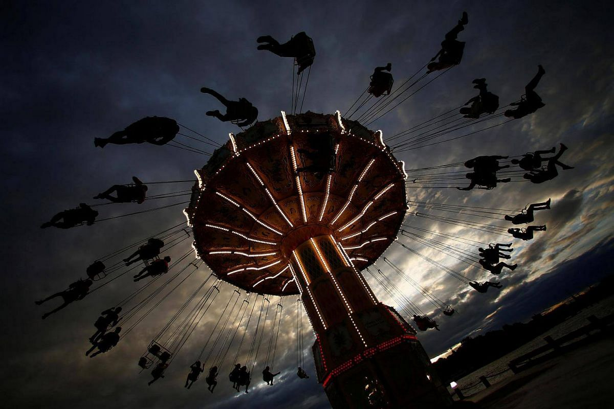 People ride on a merry-go-round carousel during sunset in Stockholm, Sweden, on August 16.