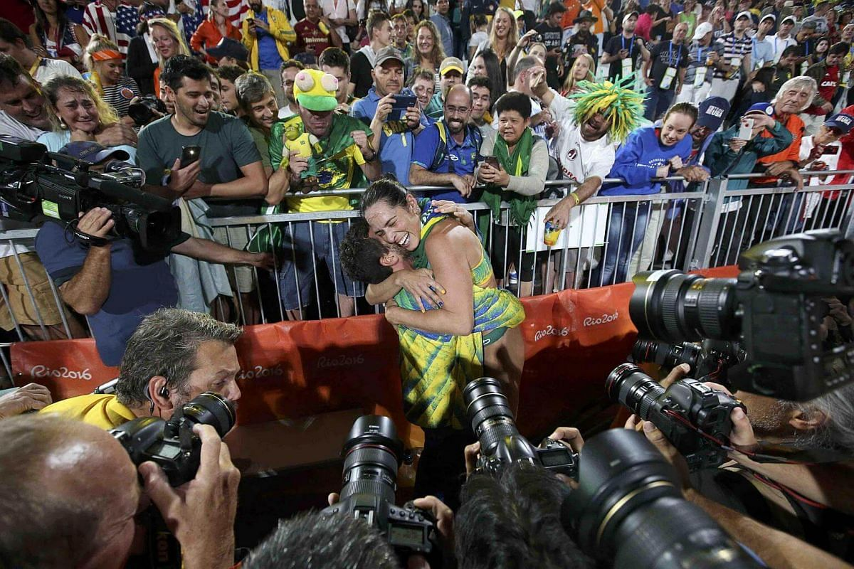 Agatha Bednarczuk of Brazil celebrates with her coach after winning the women's beach volleyball semi-final match between US and Brazil.