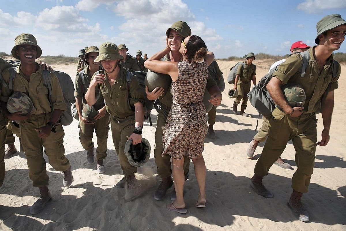 An Israeli woman kisses her son after he took part in a military parachuting exercise near Palmachim, south of the Israeli coastal city of Tel Aviv, on August 16.