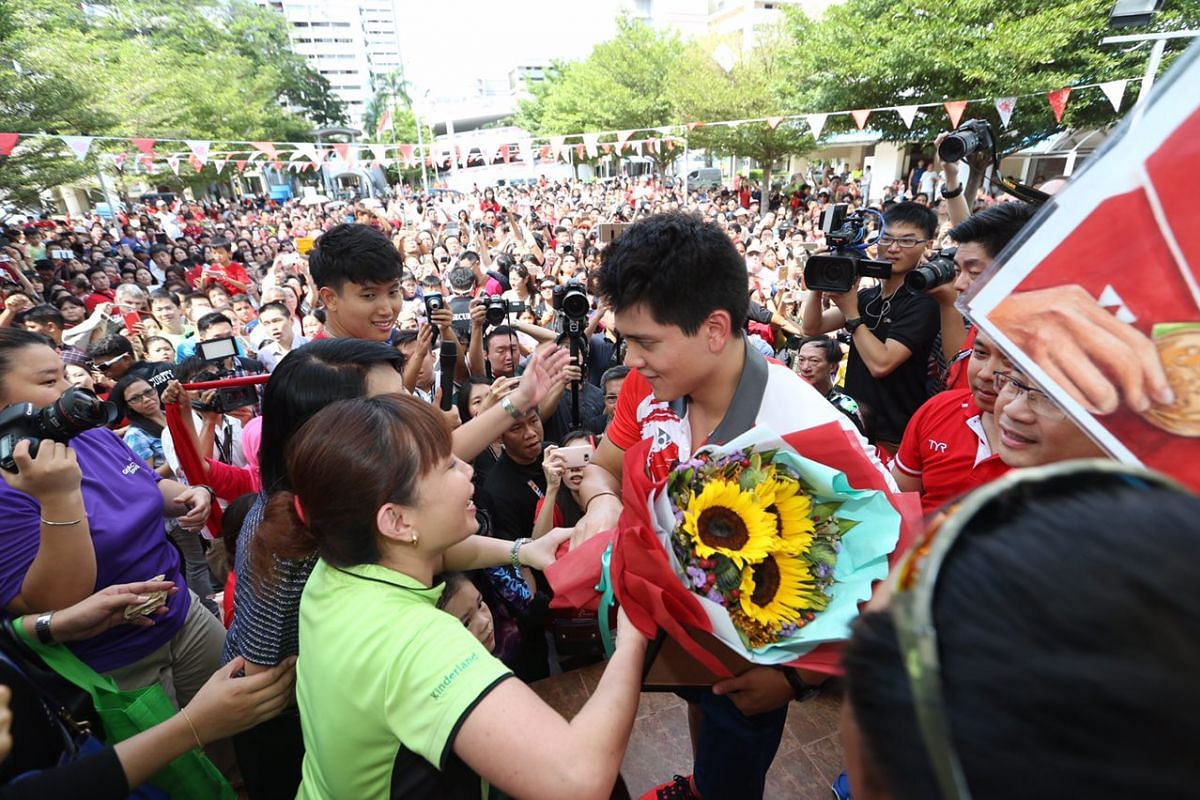 Joseph Schooling receives a bouquet of flowers from a fan at Marine Terrace.