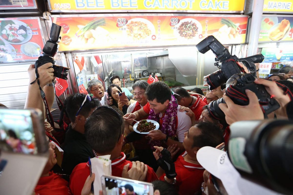 Joseph Schooling eats his favourite fried carrot cake from Bee Bee Carrot Cake at Marine Terrace Market.