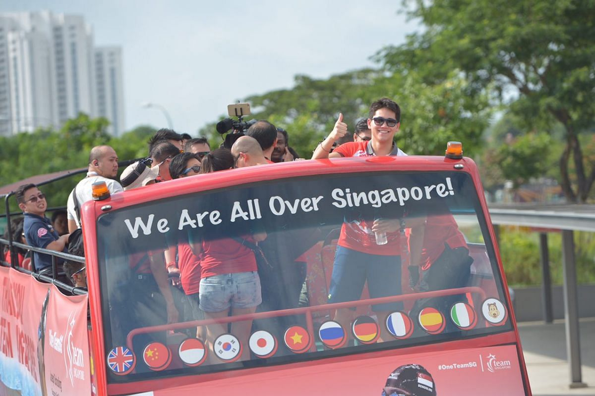Joseph Schooling gives a thumbs up as the parade bus leaves the Singapore Sports Hub for the victory parade.