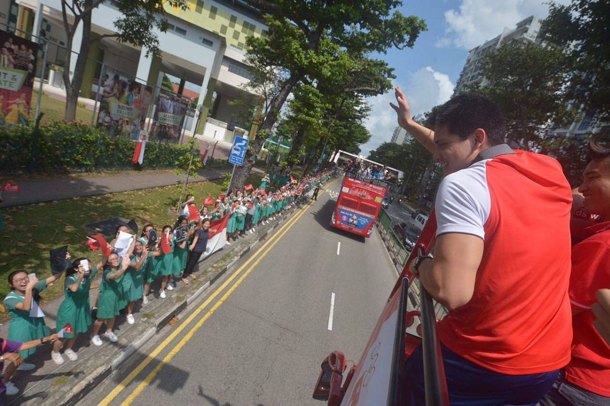 Joseph Schooling waves to fans as the parade bus passes by Tanjong Katong Girls' School.