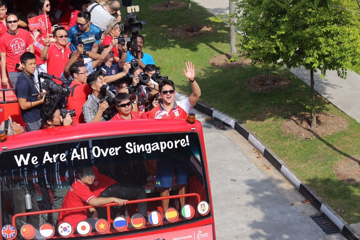 Joseph Schooling reacts as the parade bus travels along Old Airport Road.