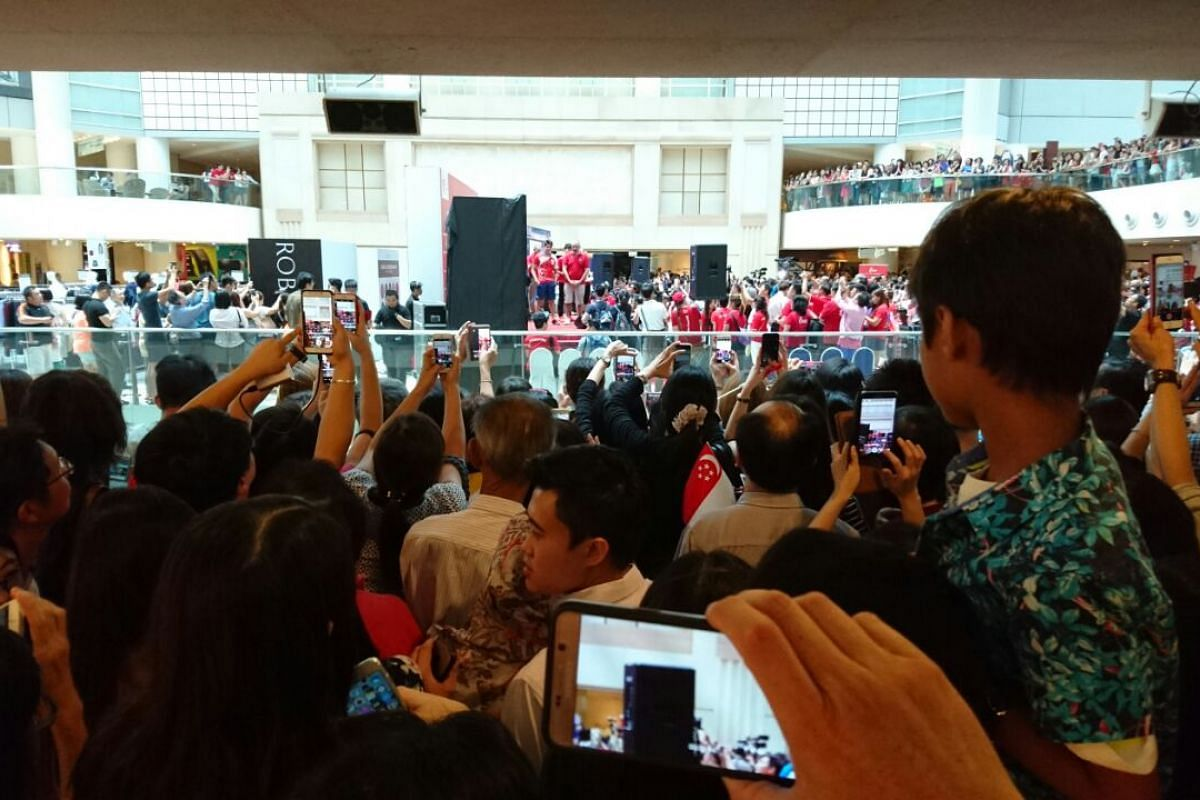 Fans hold up their handphones to take pictures of Joseph Schooling at the third and final pit stop at Raffles City.