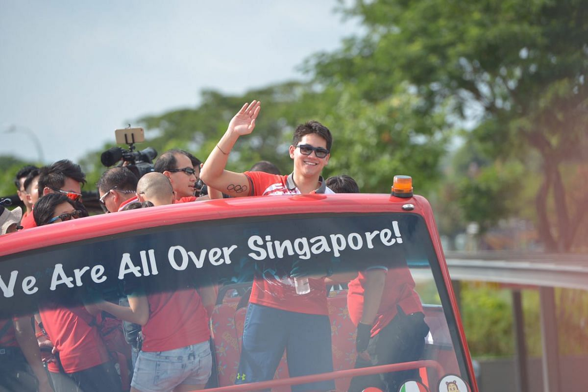 Joseph Schooling waves as the parade bus leaves the Singapore Sports Hub for the victory parade.