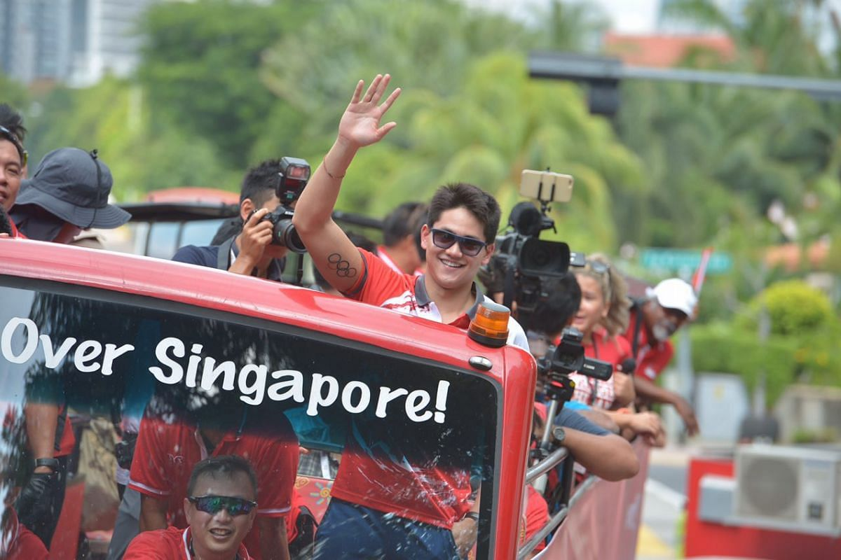 Joseph Schooling waves as the parade bus travels to the first pit stop at Marine Terrace.