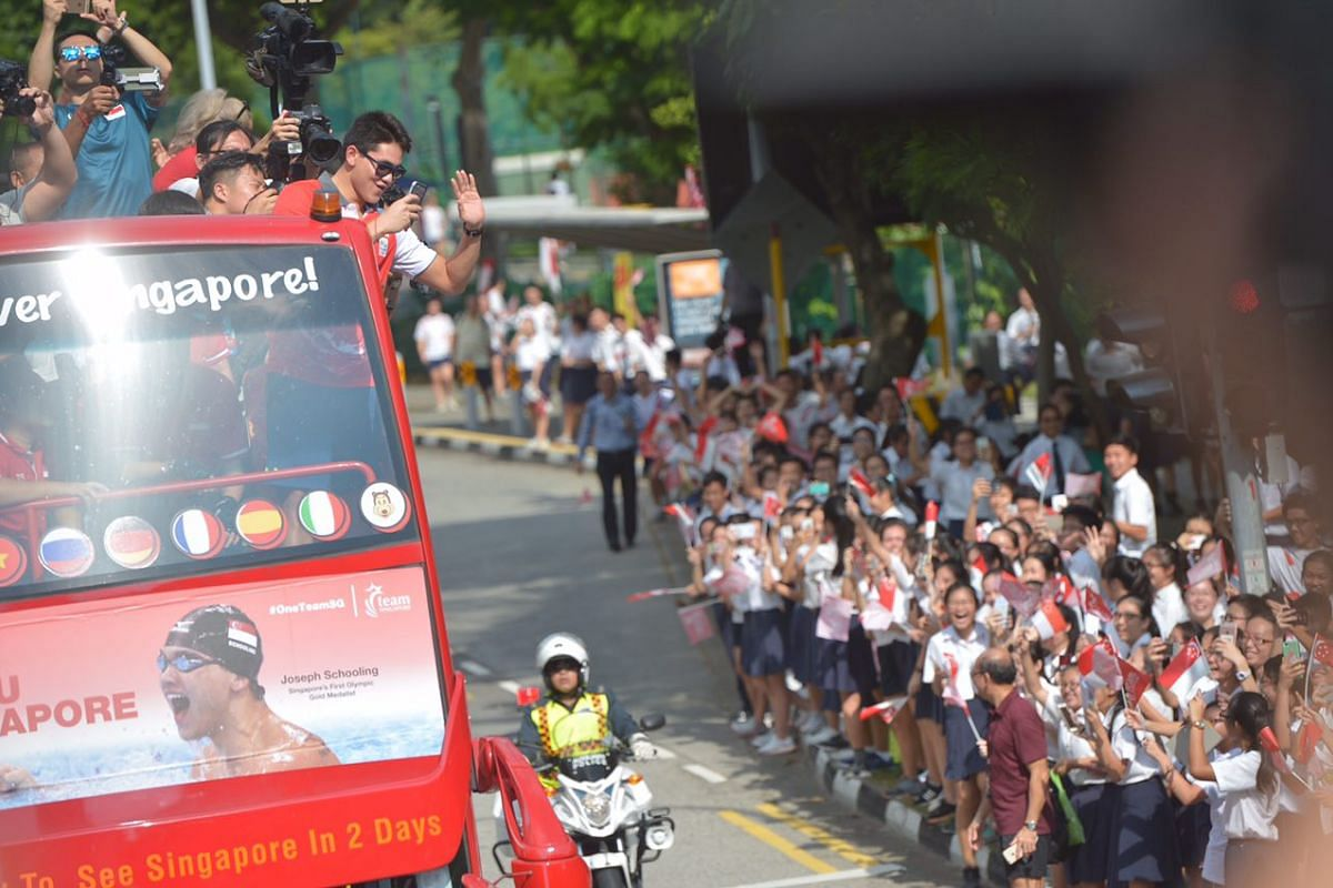 Joseph Schooling takes a picture of the crowd as the bus travels towards Marine Terrace.