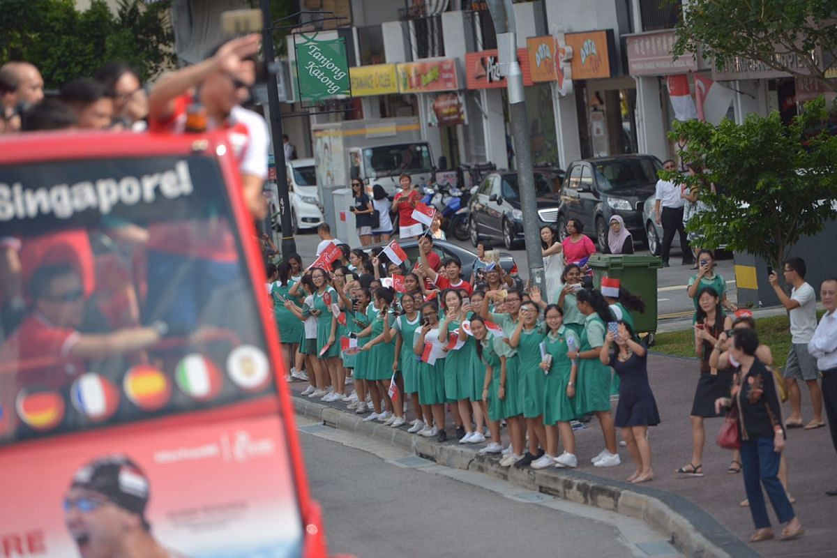 Tanjong Katong Girls' School students look on as Joseph Schooling's parade bus travels past them.