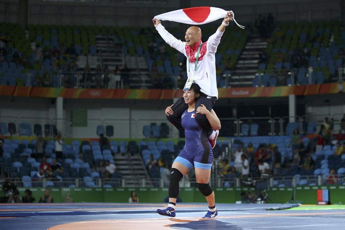 Sara Dosho of Japan celebrates with her coach after winning the gold medal in a women's freestyle final on August 17.
