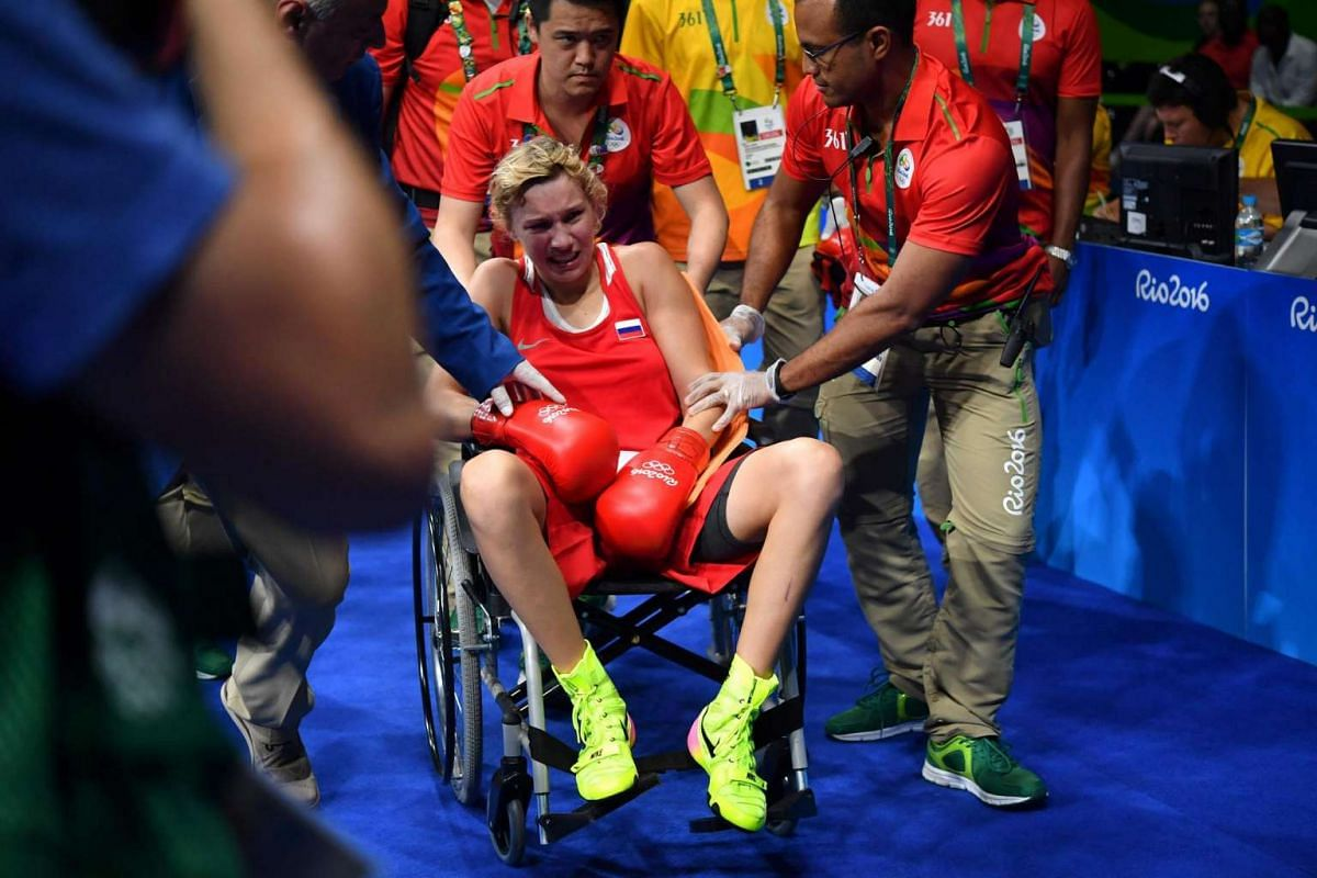 Russia's Anastasiia Beliakova is pushed in a wheelchair following an injury during her fight against France's Estelle Mossely during the women's light semi-final 2 match at the Rio 2016 Olympic Games on August 17.