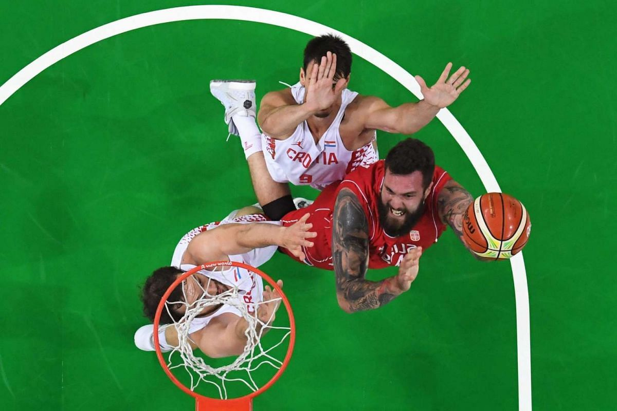 An overview shows Serbia's centre Miroslav Raduljica (right) go to the basket past Croatia's centre Miro Bilan and Croatia's forward Dario Saric during a Men's quarter final basketball match between Croatia and Serbia on August 17.