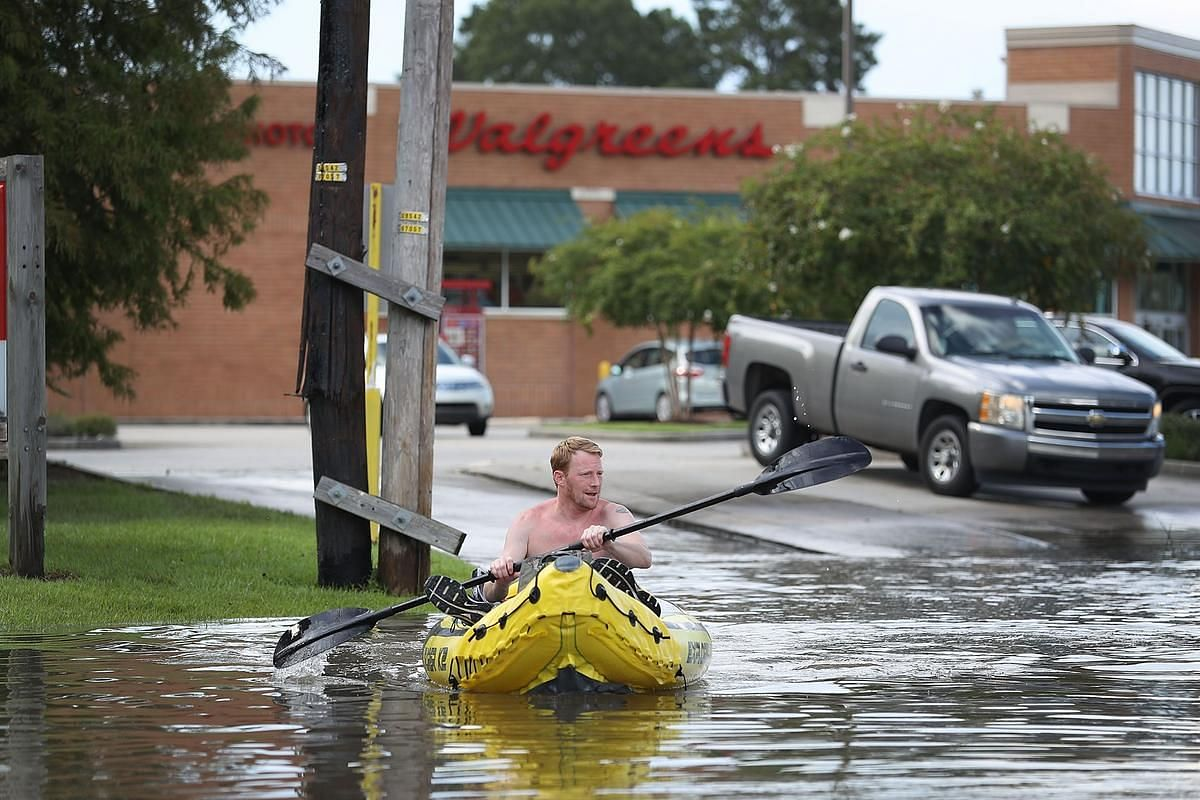 Landon Stanly navigates through a flooded street to his home on August 15 in Baton Rouge, Louisiana.