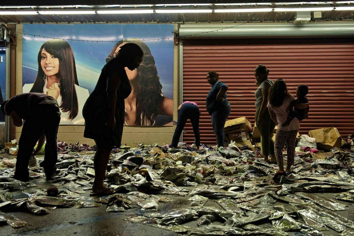 People sort through water damaged products outside Jasmine's Beauty Supply following the floods on August 16 in Baton Rouge, Louisiana.
