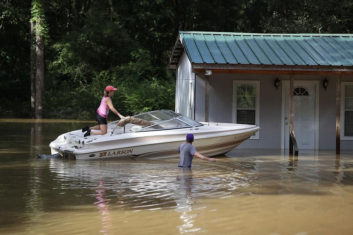 Tonya Aiken (left) and Jacques Aiken are seen with their boat in the flood waters on August 16  in Port Vincent, Louisiana.