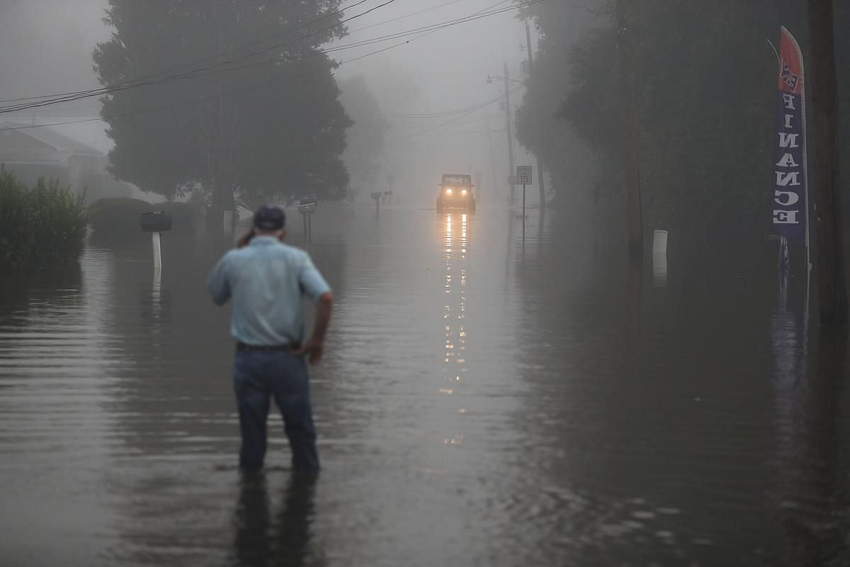 Gary Schexnayder stands in a flooded street as an early morning fog blankets the area on August 17 in Sorrento, Louisiana.