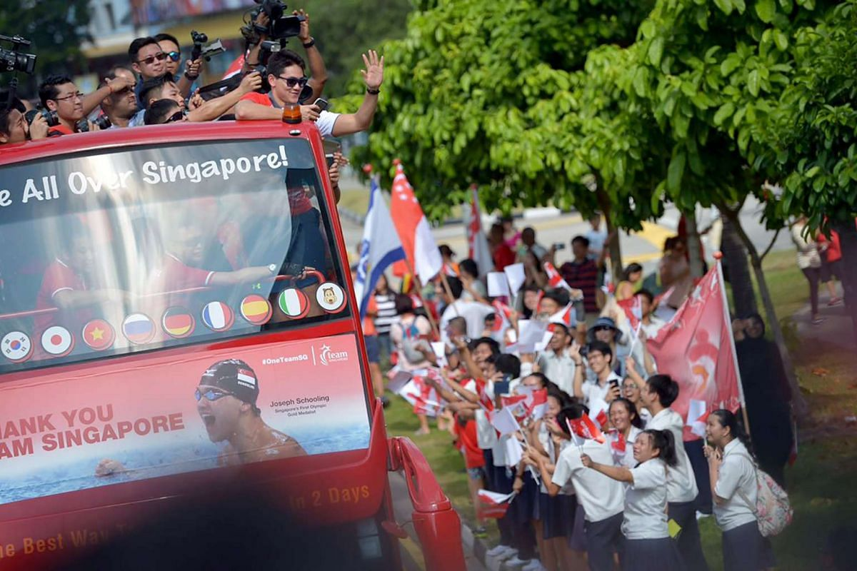 Singapore's first Olympic gold medal winner, swimmer Joseph Schooling, waving to crowd during a victory parade in an open-top bus that took him from Marine Terrace Market to SingTel Comcentre and finally, to Raffles City Shopping Centre, on Aug 18, 2