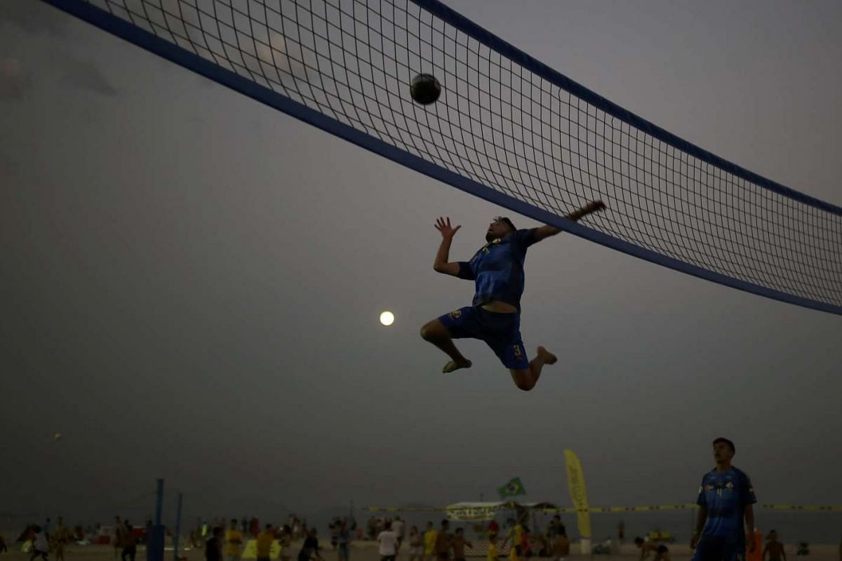 Tourists from Colombia playing bossaball, a combination of volleyball, football and gymnastics played on an inflatable court featuring a trampoline on each side of the net, on Copacabana beach on Aug 17, 2016.