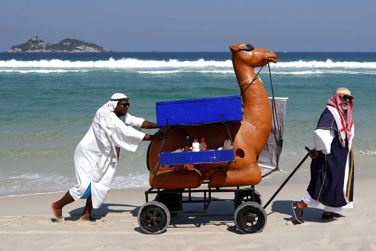 Two beach hawkers dressed as Arab men selling food and drinks from a mock camel in Praia do Pepe Beach, in theBarra da Tijuca district in Rio de Janeiro, Brazil, on Aug 17, 2016