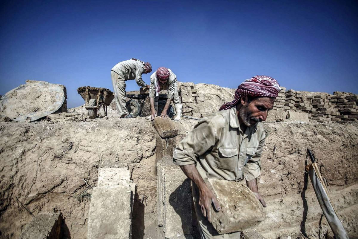 Workers move mud bricks used in the multi-layered graveyard of Douma city, outskirts of Damascus, Syria, August 18, 2016. PHOTO: EPA