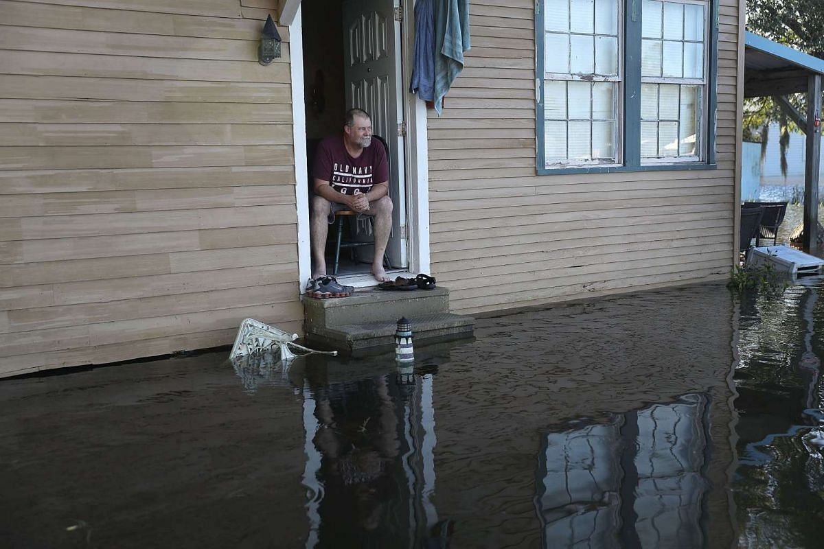 Mike Clouatre sits in a home surrounded by flood waters on August 18, 2016 in St Amant, Louisiana.  PHOTO: GETTY IMAGES/AFP