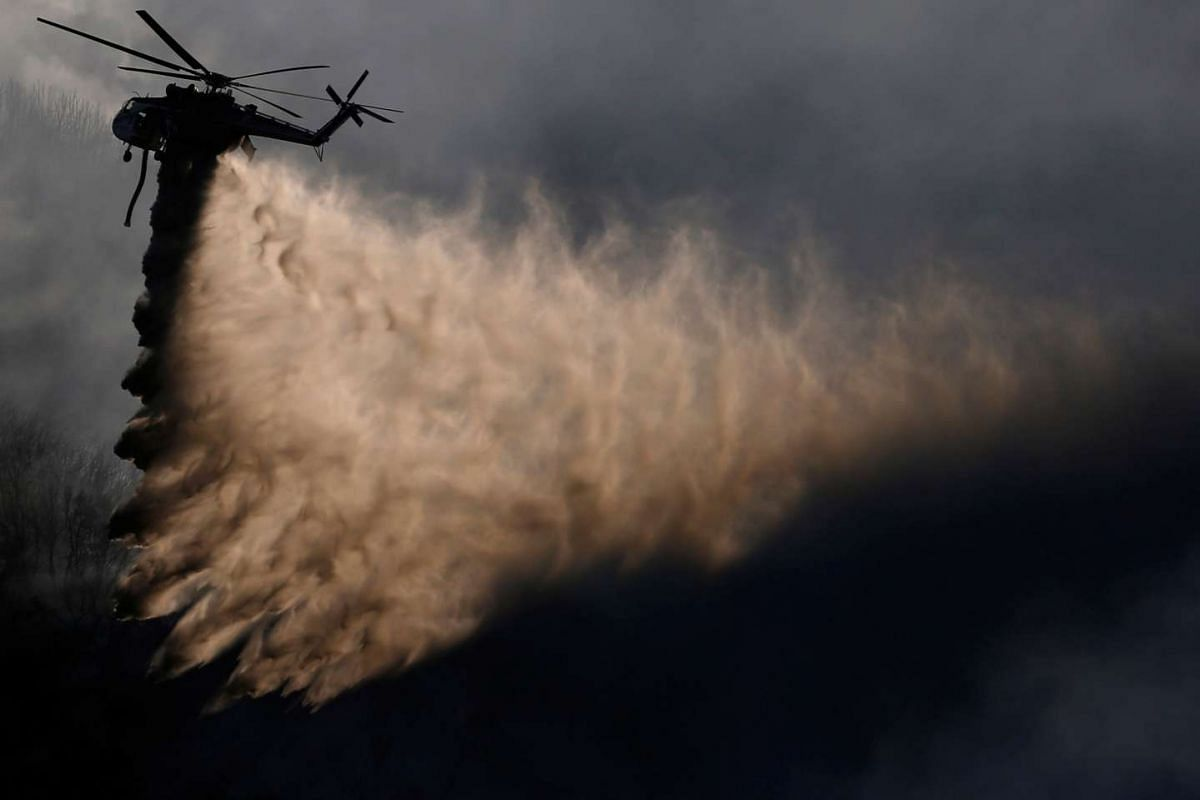 A helicopter drops water while battling the Blue Cut fire burning near Cajon Blvd in San Bernardino, California U.S., August 18, 2016. PHOTO: REUTERS