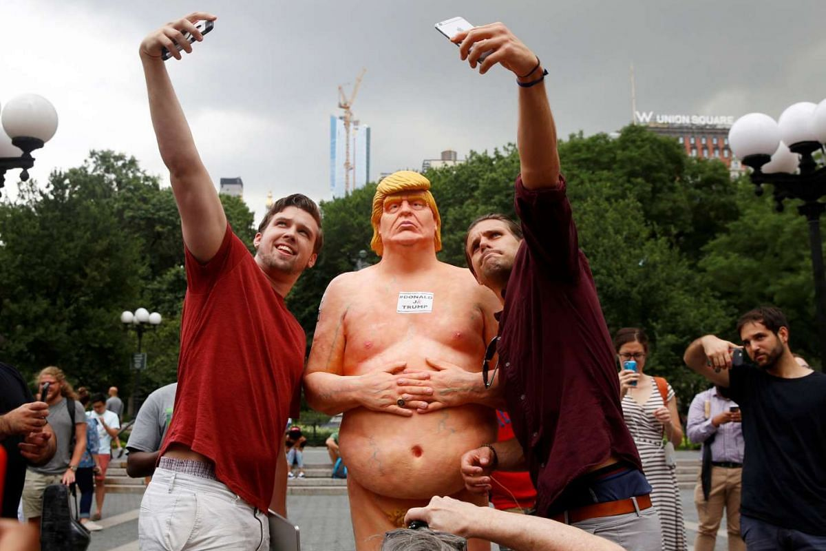 People pose for selfies with a naked statue of U.S. Republican presidential nominee Donald Trump that was left in Union Square Park in New York City, U.S. August 18, 2016. PHOTO: REUTERS