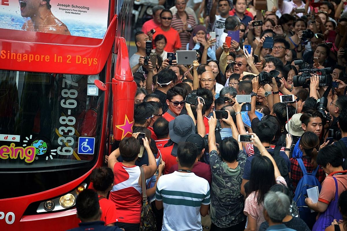 Above: Schooling and his entourage greeting the crowd as the bus pulled up at Marine Terrace Market, the first pit stop of his victory parade yesterday. Left: The swimmer surrounded by fans in Marine Terrace, where more than 1,000 residents braved th