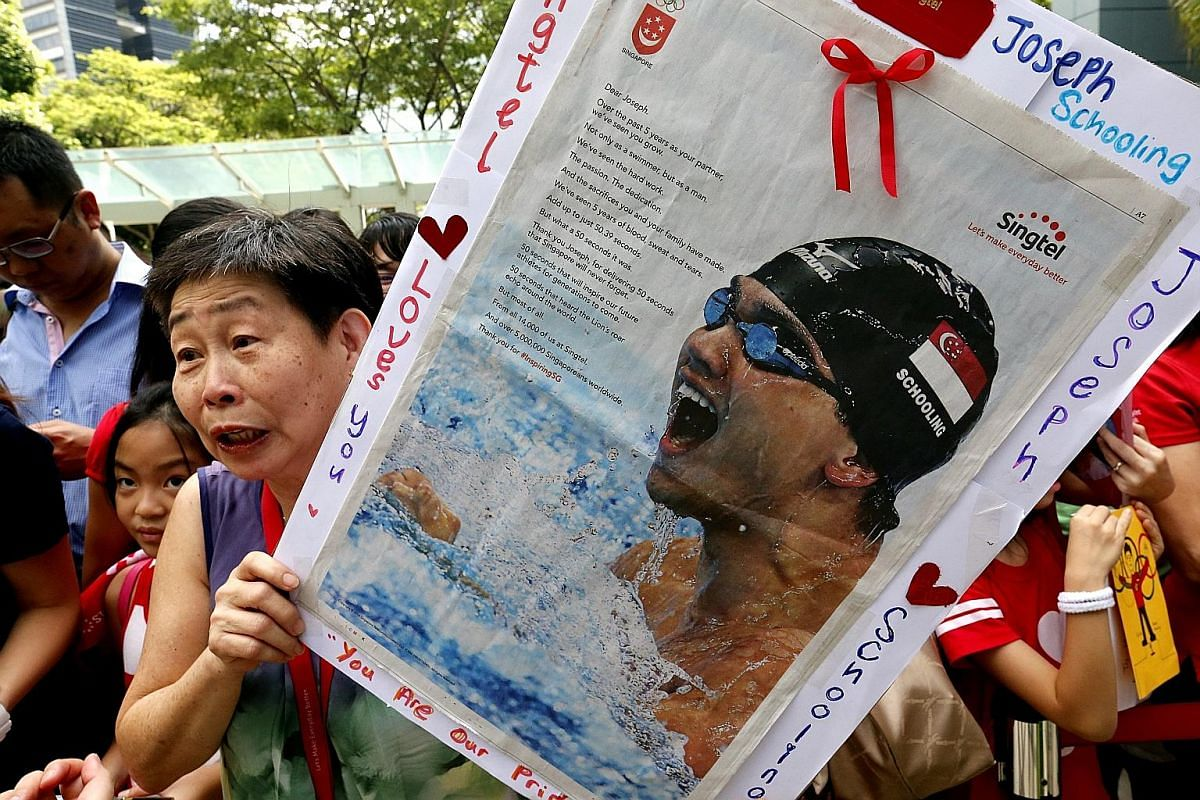 The crowd snapping photos of the swim star at the Singtel Comcentre Plaza in Somerset, where staff gave him a rousing welcome. Ms Lim Chui Hai, 65, and her 20-man team at the Singtel Comcentre made this poster for Schooling to sign. Schooling, his mo
