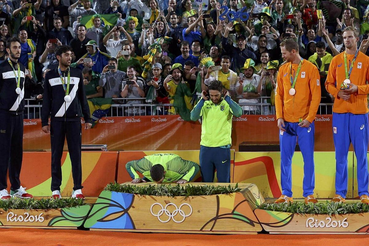 Men's beach volleyball gold medalist Alison of Brazil kisses the podium.