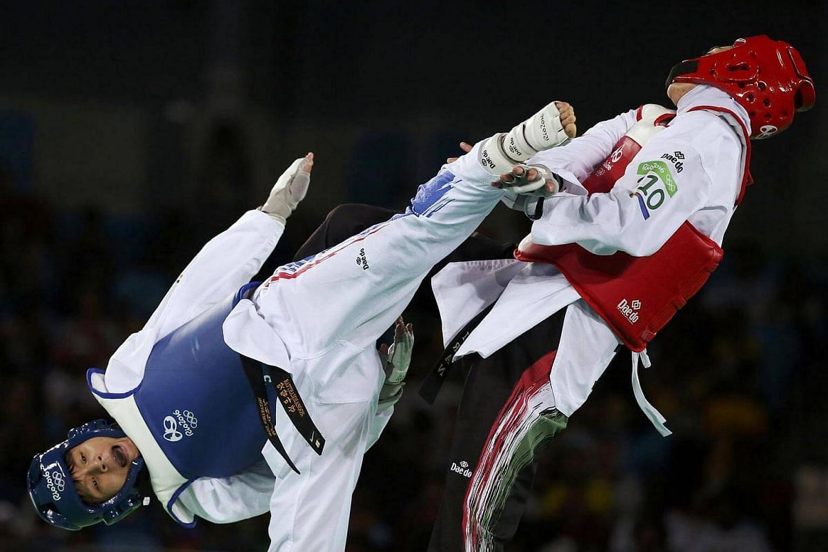 Phannapa Harnsujin of Thailand (left) competes against Kimia Alizadeh Zenoorin of Iran in the women's 57kg taekwando.
