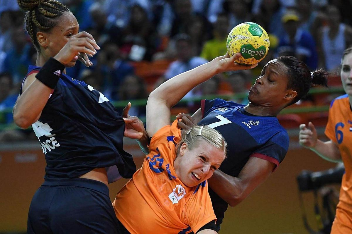 Netherlands' pivot Danick Snelder (centre) vies with France's Beatrice Edwige (left) and Allison Pineau (right) during the women's semi-final handball match.
